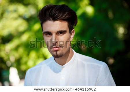 Young successful businessman smiling, looking at camera, walking around sunny city.