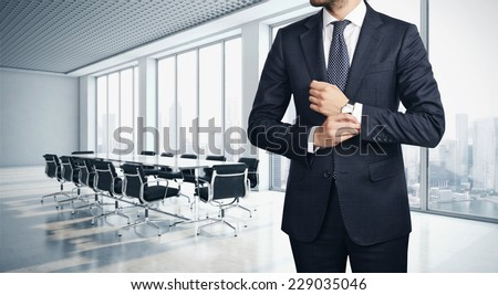 Young successful businessman standing in contemporary office - stock photo