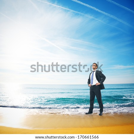 Young successful businessman standing on a tropical beach