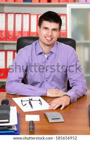 Young successful businessman working on his desk, inside office.