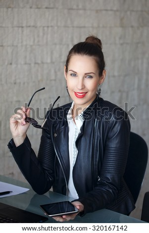 Young successful businesswoman in leather jacket holding sunglasses and tablet - stock photo