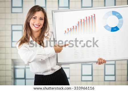 Young successful businesswoman showing growth profit diagram and looking at camera.