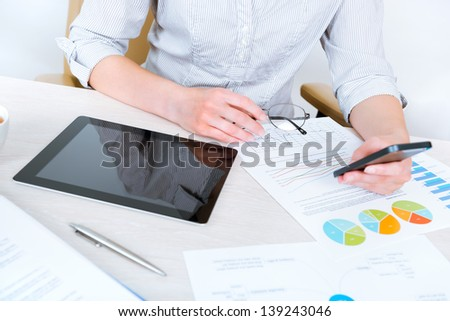 Young successful businesswoman wearing in casual shirt and sitting at desk in the office and using mobile phone for business communication - stock photo