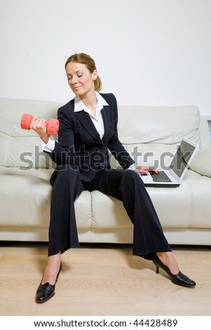 Young successful businesswoman with dumbbells and laptop - stock photo
