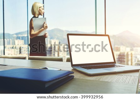 Young successful businesswoman with paper document in hands is looking in office window with view of New York city. Open laptop with mock up copy space screen for your content is lying on a table - stock photo