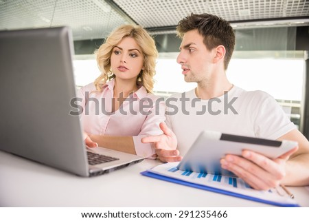 Young successful couple dressed casual sitting at office and discussing business plan.