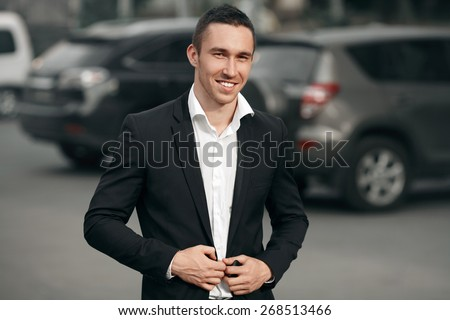 Young successful smiling man in a black suit, on the street, on the background of cars. Happy modern man. Outdoors - stock photo