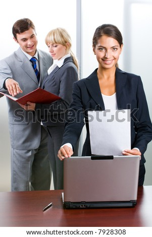 Young successful woman is standing near her co-workers and looking at camera in the office