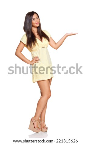 young sun-tanned woman  dressed in a lite summer yellow dress  showing open palm presenting something, isolated on white background - stock photo