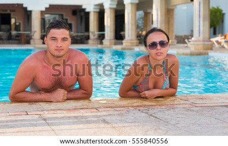 Young suntanned couple relaxing in a swimming pool with columns in antique style at the hotel