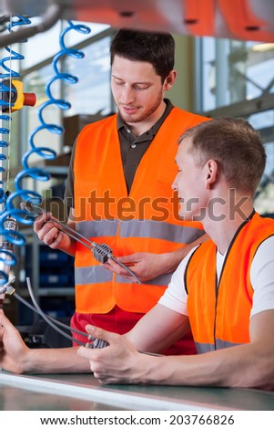 Young supervisor and production worker in orange protective vests - stock photo