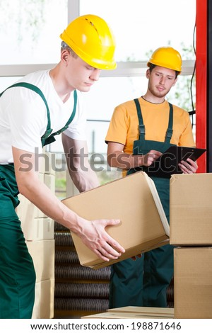 Young supervisor and warehouse worker during job - stock photo