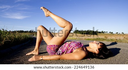 Young supple dancer lying on the back on a french country road. She raises gracefully her leg. - stock photo