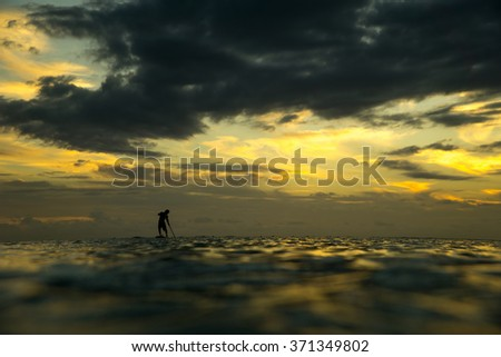 Young surfer coming back from the ocean by paddle boards. He is rowing against the backdrop of a beautiful sunset in Mauritius - stock photo