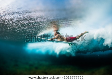 Young surfer dives under the ocean wave with surf board and performs trick named in surfing as a Duck Dive. Tilt shift effect applied