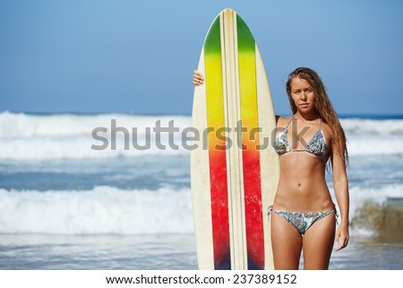 Young surfer girl standing with surfboard on the beach, beautiful hot bikini model on summer travel vacation engage water sports, teenager girl in swimsuit holding her surfboard smiling