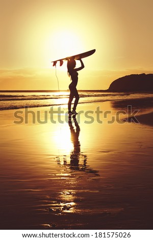 young surfer girl with surfboard at sunrise - stock photo