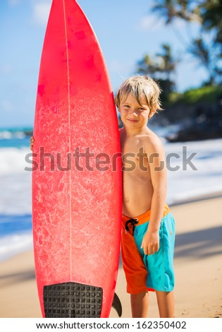 Young surfer, happy young boy at the beach with surfboard - stock photo