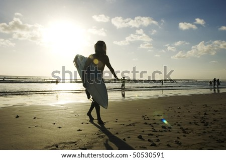 young surfer holding a surf board on the beach in Kuta, Bali, Indonesia - stock photo