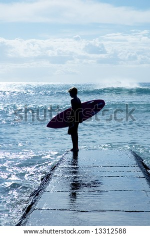 Young surfer looking at the waves - stock photo