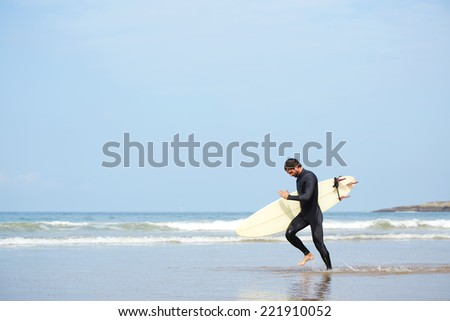 Young surfer man carrying his surfing board running along the ocean to waves, guy with surfboard running touching waves, professional surfer man dressed in wetsuit ready to surfing runs to the waves