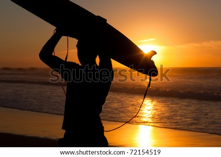 Young surfer on the beach with his surf board over the head, looking at the ocean - stock photo