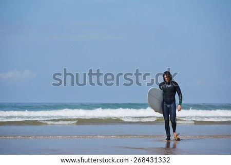 Young surfer sport man carrying his surfing board and going out the sea while on vacation during a sunny day, with an intense blue sky and big waves break on background - stock photo