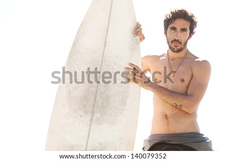 Young surfer sports man standing on a beach while wearing a neoprene rubber surfing suit during a sunny day, being thoughtful and holding a surfing board upright during a sunny day. - stock photo