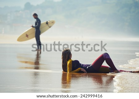 Young surfer standing on a beach holding a surfboard with a girl lying on sand on the foreground - stock photo