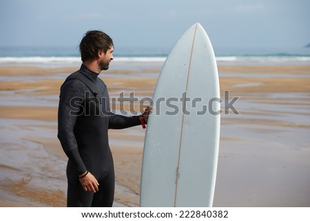 Young surfer standing on ocean beach enjoying amazing view, handsome brunette surfer holding his board stand on the beach waiting waves, surfer man with surfing board looking along the shore - stock photo