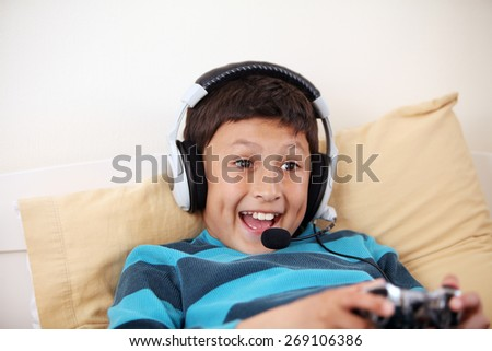 Young surprised boy playing video game with his friends with headset and microphone with copy space