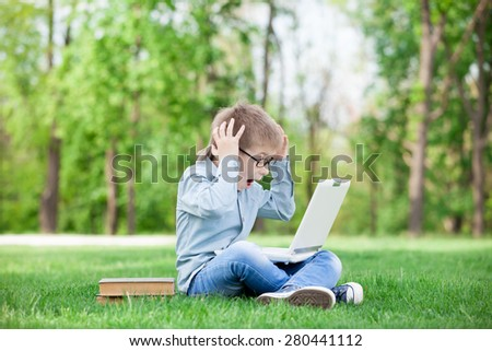 young surprised boy with a books and laptop computer on green grass in the park - stock photo