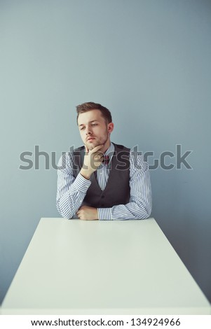 Young surprised business man in bowtie and jacket sitting at the table - stock photo