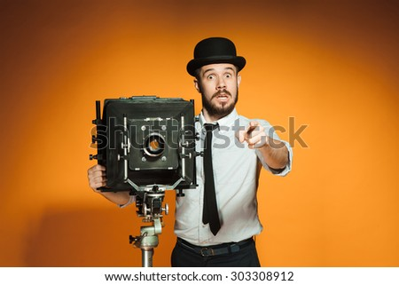 Young surprised man in hat as photographer with retro camera pointing to you on an orange background - stock photo