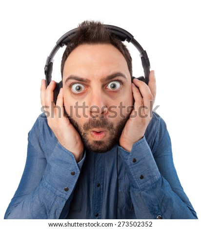 Young surprised man with headphones on white background.