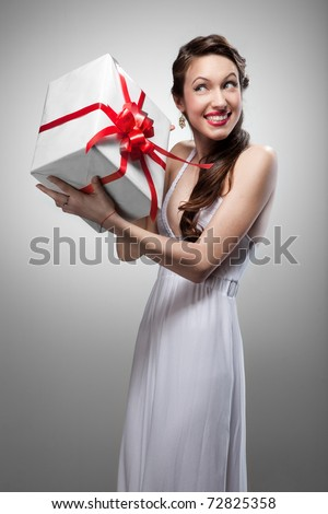 Young surprised smiling woman holding gift