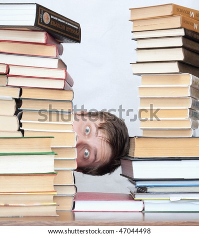 Young surprised student hide behind stacked books