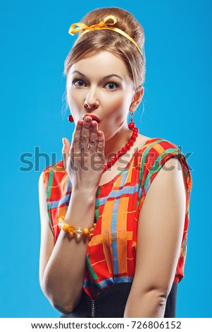 Young surprised woman in colorful old-fashion clothes in pinup style