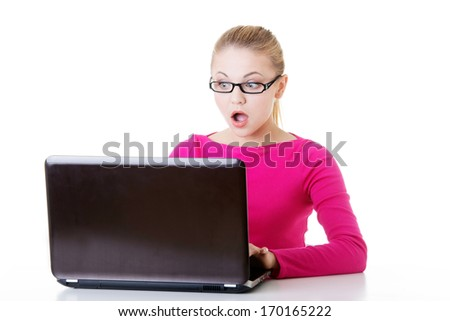 Young surprised woman sitting in front of laptop. Isolaed on white. - stock photo