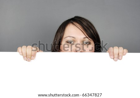 Young surprised woman with a blank billboard - stock photo
