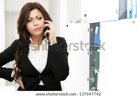Young suspicious business woman talking ah the phone on office background - stock photo