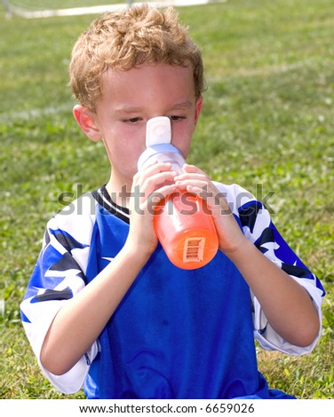 Young sweaty red faced boy taking drink at halftime of soccer game - stock photo