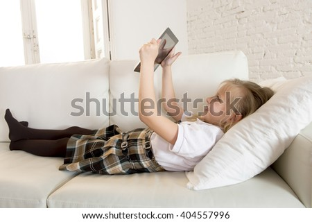 young sweet cute and beautiful 6 or 7 years old girl with blond hair in school uniform lying on home sofa couch using internet app on digital tablet pad playing online game smiling happy - stock photo