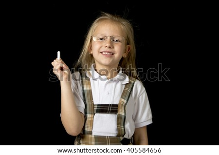 young sweet junior schoolgirl with blonde hair standing happy and smiling isolated in black background holding chalk wearing school uniform in children education success and fun - stock photo