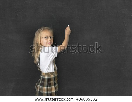 young sweet junior schoolgirl with blonde hair standing happy and smiling writing with chalk copy space in school classroom blackboard wearing school uniform in children education - stock photo