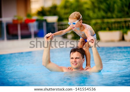 young swimmer boy on swim start at swimming pool ready for jump race and win. Father teach her son to swim. - stock photo