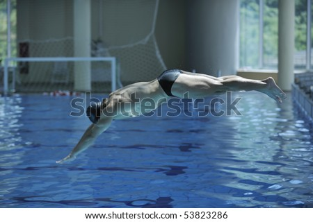 young swimmer on swim start at swimming pool ready for jump race and win - stock photo