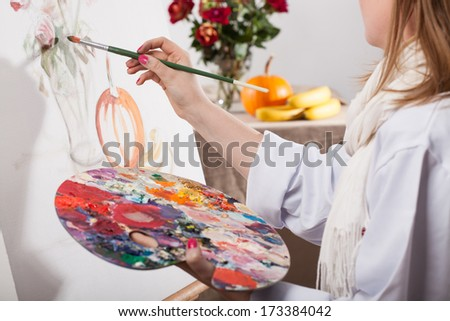 Young talented woman painting a nature on white canvas - stock photo