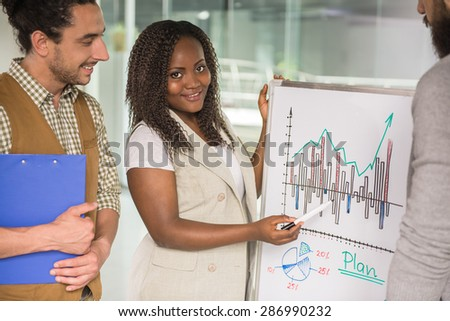 Young talented woman showing to colleagues new business strategy. - stock photo