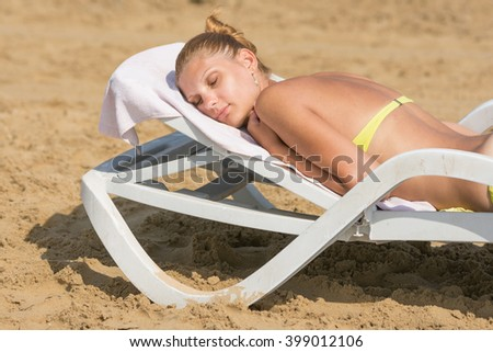 Young tanned woman lying on a deck chair with his eyes closed on the beach - stock photo